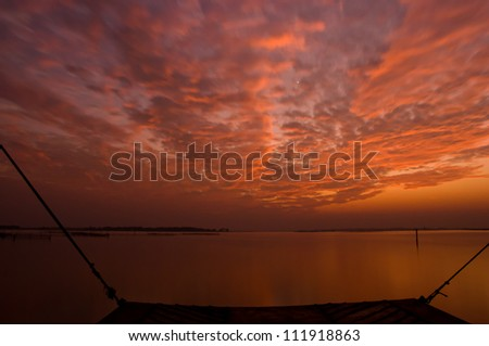 Dramatic golden orange sunset over Asia's largest salt water lake in Chilika, India - stock photo