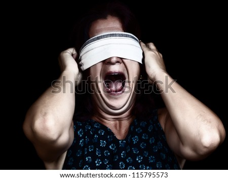 Dramatic image of a frightened woman screaming   and covering her eyes to avoid seeing isolated on black (useful to illustrate crime, gender violence or discrimination) - stock photo
