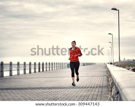 Dramatic image of a very active woman busy running on the promenade along the ocean side to keep up her fitness levels as much as possible - stock photo