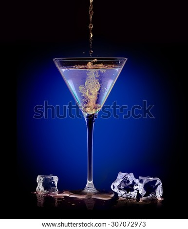 Dramatic image on dark blue of the mixing and blending of two alcoholic beverages when pouring a mixer into a martini in a conical glass flanked by ice cubes. Party concept - stock photo