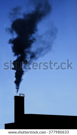 Dramatic industry chimney silhouette exausting co2 in the atmosphere. - stock photo