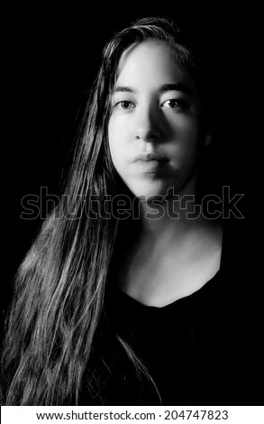 Dramatic low-key Rembrandt lighting portrait of an 18 year old young woman with long hair on black background in black and white (B&W) - stock photo