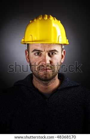 dramatic manual workwer portrait on dark background - stock photo