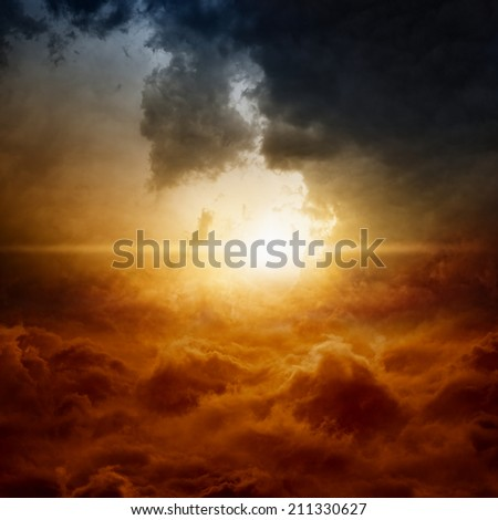 Dramatic nature background - bright sun in dark stormy sky - stock photo