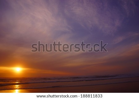 Dramatic ocean sunset with clouds and blue sky  near Yaquina Head, Newport, Oregon coast  - stock photo