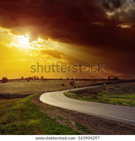 dramatic orange sunset over road - stock photo