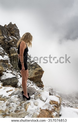 Dramatic photo of a beautiful girl standing on the edge of an abyss high in the snowy mountains. She is looking down. Stormy weather with falling snow - stock photo