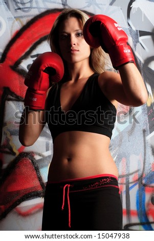 Dramatic photo of female boxer with red gloves pose in front of graffiti - stock photo