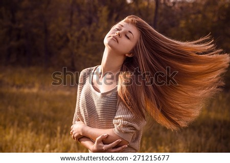 Dramatic portrait of a girl theme: portrait of a beautiful girl with flying hair in the wind against a background in the forest - stock photo