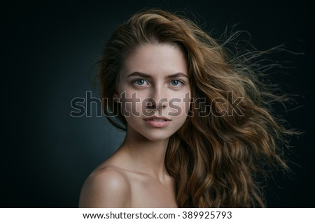 Dramatic portrait of a girl theme: portrait of a beautiful girl with flying hair in the wind against a background in studio - stock photo