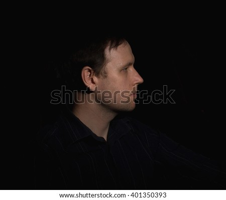 Dramatic portrait of a man in a low key. People - stock photo