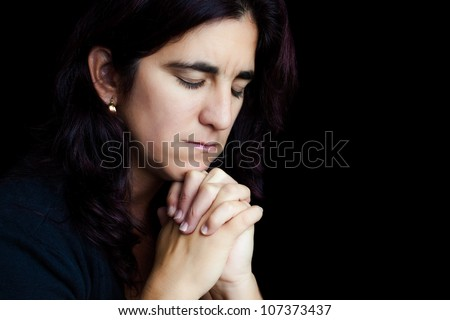 Dramatic portrait of a sad hispanic woman praying isolated on black with space for text - stock photo