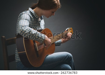 Dramatic portrait of a young woman playing the guitar while sitting on an old wooden chair. Studio portrait with copy space. - stock photo