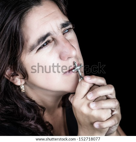 Dramatic portrait of an hispanic woman praying and kissing a crucifix (isolated on black) - stock photo