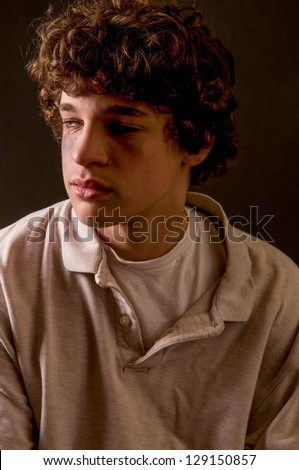 dramatic portrait of battered, beaten teen boy, crying - stock photo