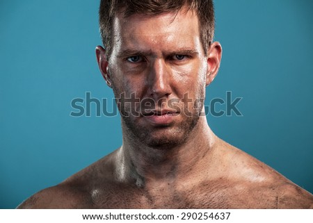 Dramatic portrait of young dirty man isolated on blue background - stock photo