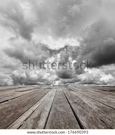 Dramatic raincloud in the horizon of an empty grungy timber deck platform.  - stock photo
