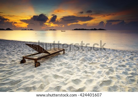 Dramatic ray of light in the beautiful sunrise morning at the tropical white sand beach with wooden chair - nature and travel concept - stock photo