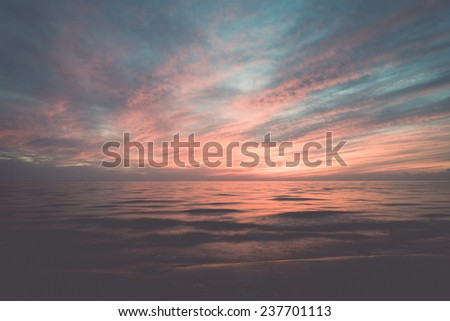 dramatic red sunset over the baltic sea shore - retro, vintage style look - stock photo