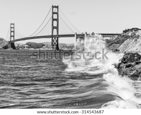 Dramatic scene of pacific waves crashing in front of the Golden Gate Bridge - stock photo