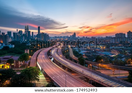 Dramatic scenery of elevated highway heading towards Kuala Lumpur city centre during sunset - stock photo