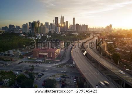Dramatic scenery of elevated highway heading towards Kuala Lumpur city centre during sunset. - stock photo