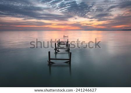 Dramatic scenery sunset with lonely broken bridge - stock photo