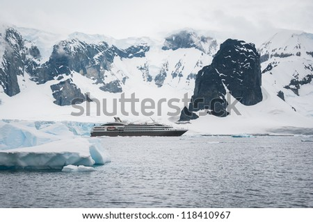 Dramatic seascape in Antarctica, cruise ship in the sea - stock photo