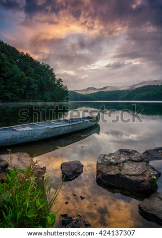 Dramatic sky and calm lake with canoe - stock photo