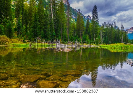 Dramatic Sky and mountain peaks reflection in Cascade Creek - Grand Tetons - stock photo