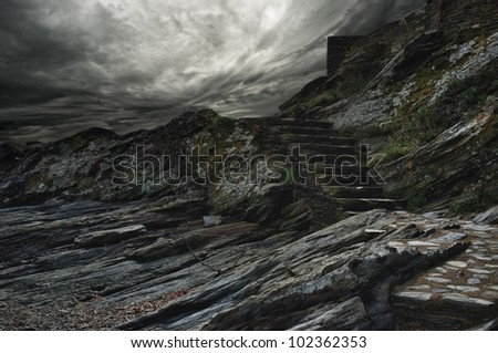 Dramatic sky over steps in a mountain. - stock photo