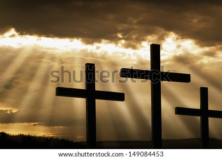 Dramatic sky silhouettes three wooden crosses with shafts of sunlight breaking through the clouds. A dramatic and inspiring religious photographic illustration for Easter or Christian beliefs  - stock photo