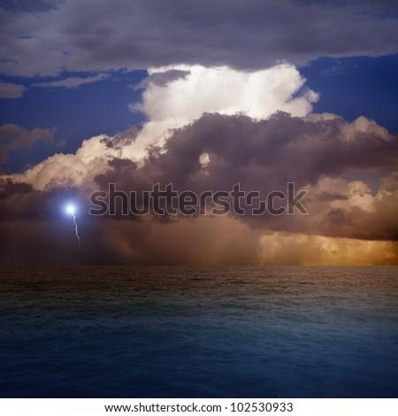 Dramatic sky with lightning, sea, sunset - stock photo