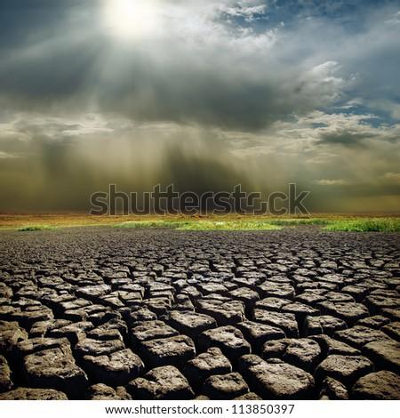 dramatic sky with sun over drought earth - stock photo