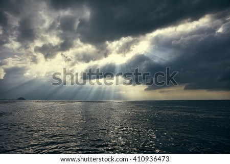 dramatic sky with sun rays over the sea. Nature background - stock photo