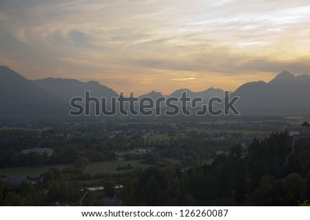 Dramatic sunlight over Salzburg valley with mountains in distance - stock photo