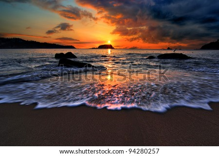 Dramatic sunrise on a Pacific coast beach in Mexico - stock photo