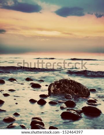Dramatic sunrise on a rocky beach. Retro, vintage style - stock photo