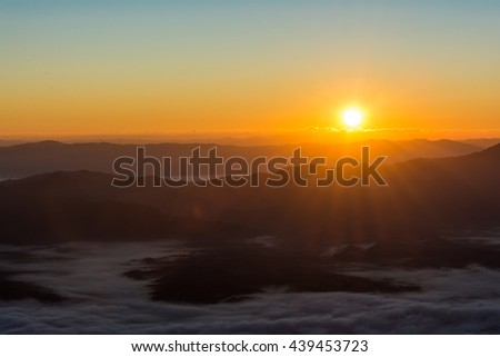 Dramatic sunset and sunrise sky with flare and the sun goes up or down behind silhouette of cloud and mountain layer. - stock photo