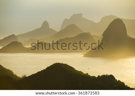 Dramatic sunset city skyline scenic overlook of Rio de Janeiro, Brazil with backlit silhouettes of Sugarloaf Mountain, Niteroi, and Guanabara Bay - stock photo