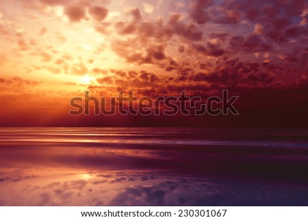 dramatic sunset in purple clouds over sea - stock photo
