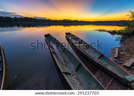 Dramatic sunset in the Amazon rain forest in Bolivia in Madidi National Park with two canoes in the foreground - stock photo
