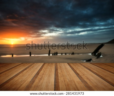 Dramatic sunset landscape over shipwreck on Rhosilli Bay beach with wooden planks floor - stock photo