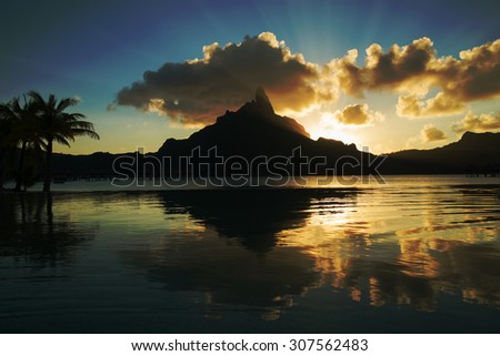 dramatic sunset on Mount Otemanu through lagoon and infinity pool on the tropical island Bora Bora, honeymoon destination, near Tahiti, French Polynesia, Pacific ocean - stock photo