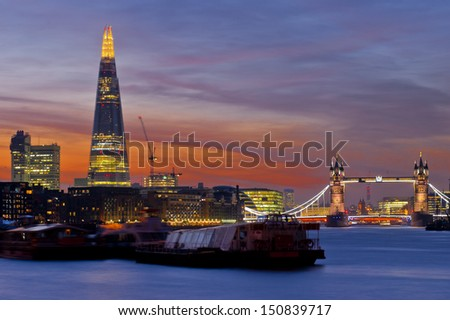 Dramatic sunset on the new London skyline with Tower Bridge and the new The Shard skyscraper. Long exposure, shot 2013. - stock photo