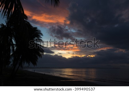 Dramatic sunset on the ocean on  background of palm trees. Pink clouds. Dusk. Fiji. - stock photo
