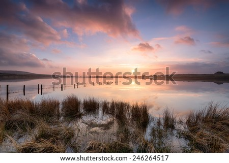 Dramatic sunset over Dozmary Pool a small mysterious lake on Bodmin Moor in Cornwall where legend has it that King Arthur threw his famous sword Excalibur back to the Lady of the Lake - stock photo