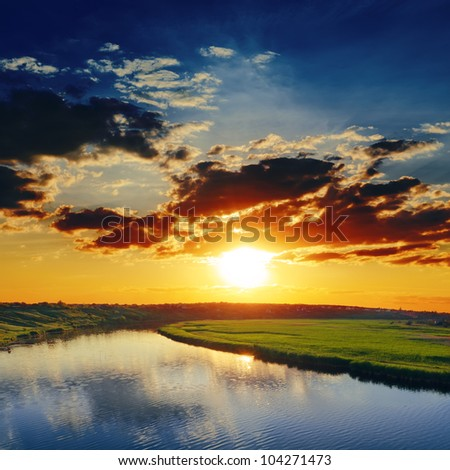 dramatic sunset over river - stock photo