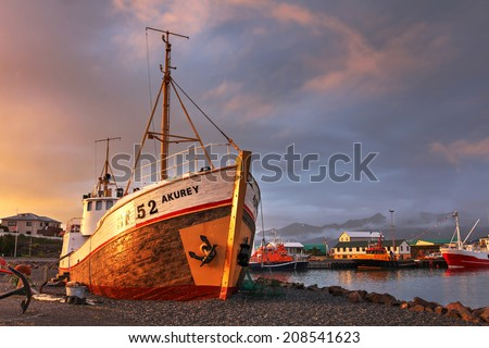 Dramatic sunset over the Hofn harbor in south-eastern part of Iceland. The composition focuses on the shipwreck of an old fishing boat, nowadays decorating the harbor. - stock photo