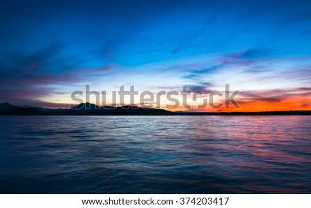 Dramatic sunset over the lake in the Swiss Alps. Canton Zug. In the background the mountains silhouettes. High Dynamic Range Image - stock photo